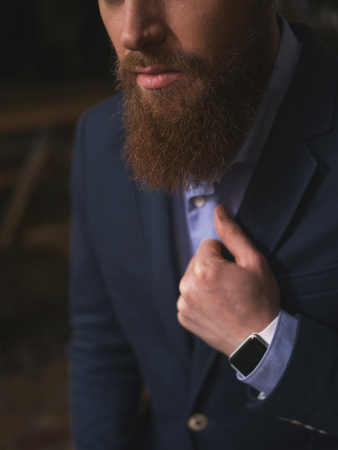 seriousness: Cheerful man with a beard is expressing his seriousness. He is sitting and adjusting the collard of a blue jacket. The man has a smart watch on his arm