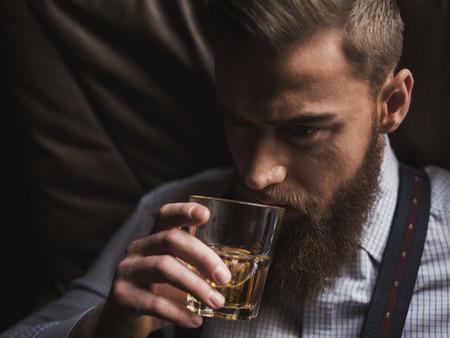 hombre con barba: Retrato de hombre disfruta de la bebida de alcohol rica atractiva. Él está sentado y relajante. El hombre está mirando hacia adelante con confianza