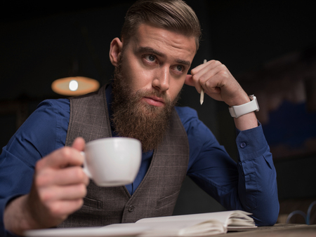 article writing: Skillful young journalist is writing the article. He is sitting at the desk. The man is drinking a cup of coffee and looking forward thoughtfully