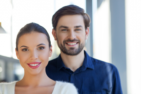 freelancers: Portrait of two cheerful freelancers are ready to work. They are standing and smiling. The man and woman are looking at the camera with joy
