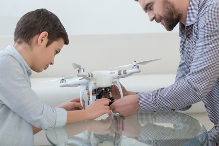 seriousness: Cute father is teaching his son to operate the drone. The boy is looking at the drone with seriousness. The man is smiling Stock Photo