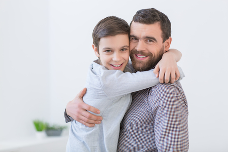 Portrait of father and son embracing and smiling. The man is holding a boy and looking at camera happily