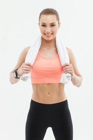 resting heart rate: Pretty runner is making a break after jogging. She is wiping her sweat with a towel and smiling. The woman is standing and looking at camera happily. Isolated