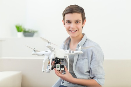 Cheerful boy is holding a small white drone. He is sitting on sofa and looking forward playfully. The teenager is smiling