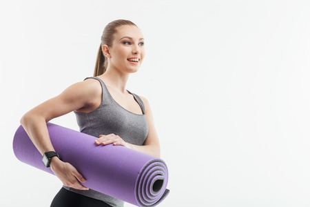 Waist up portrait of beautiful slim girl carrying an exercise mat. She is standing and looking aside with happiness. Isolated and copy space in right side
