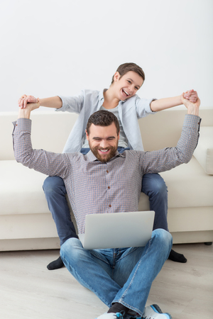 disturbing: Cheerful boy is disturbing his father from work on laptop. He is sitting on sofa and holding male hands for fun. The boy and man are smiling