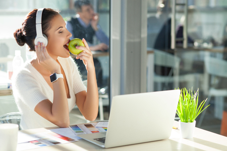 break from work: Beautiful young freelancer is relaxing after work. He is listening to music from headphones with enjoyment. The woman is sitting at the desk and eating an apple