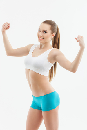 boasting: I am very strong. Portrait of attractive young woman boasting of her fit body and smiling.  She is raising arms and showing her muscles. Isolated