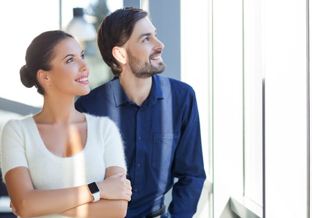 freelancers: Cheerful young freelancers looking through the window dreamily. They are standing in office. The man and woman are smiling Stock Photo