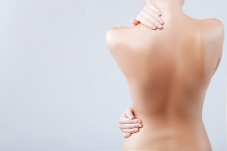 nude young: Девушка стоит и осторожно касаясь ее тела.