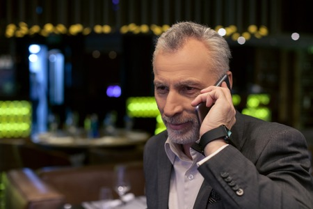 busy beard: Cheerful mature businessman is using a mobile phone for communication. He is standing and smiling in restaurant