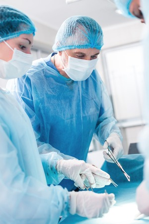 seriousness: Professional male surgeon is operating on a patient. He is holding surgical instruments and looking down with concentration. His female assistant is standing and helping with seriousness Stock Photo