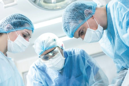 Experienced surgeons are trying hart to save human life. They are standing and looking down seriously