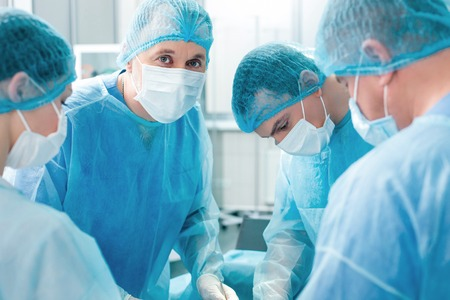 Professional surgeons are trying to save human life in surgery. They are standing and doing the operation with concentration. The mature doctor is looking at camera with joy