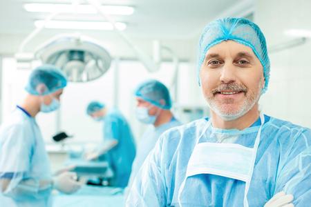 cirujano: Los cirujanos profesionales se están preparando para la operación. Senior médico está de pie y mirando a la cámara con confianza. El está sonriendo