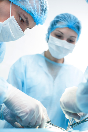 seriousness: Now we will safe human life. Skillful male surgeon is performing and operation with seriousness. He is standing and holding instruments. His female assistant is helping