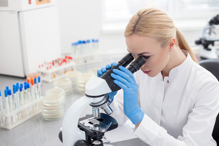 seriousness: Cheerful young scientist is making analysis of samples. She is looking through the microscope with seriousness. The woman is sitting at the table in laboratory