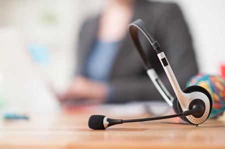 recepcionista: Cierre de auriculares en el mostrador. Operador de sexo femenino joven est� sentada y utilizando equipo port�til en el fondo