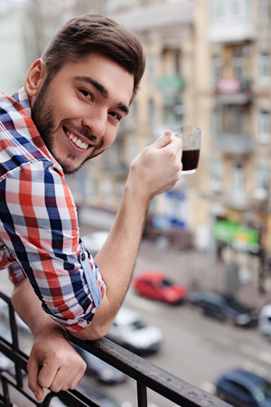 hot guy: Cheerful young man is enjoying hot coffee and smiling. He is standing on balcony and looking at camera happily
