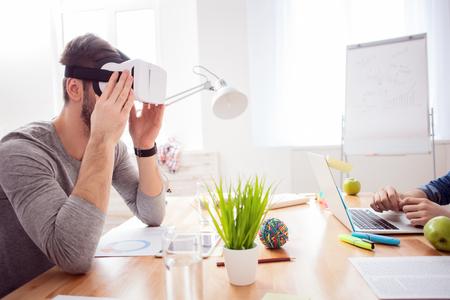 Vrolijke jonge beambte kijkt naar een virtual reality-apparaat met belangstelling. Hij zit aan de balie. Zijn collega is aan het typen op de laptop