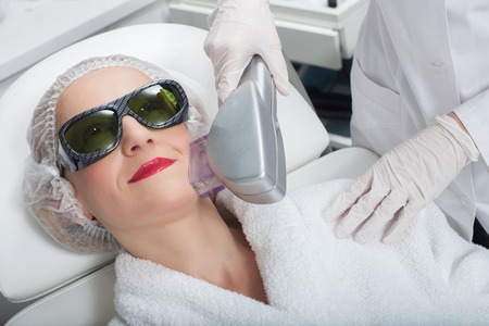 aging woman: Cheerful senior woman is preventing aging by laser therapy. She is lying and smiling. The beautician is holding equipment near her face