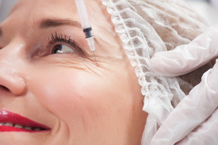 Close up of female face getting a collage injection with hyaluronic acid by beautician.