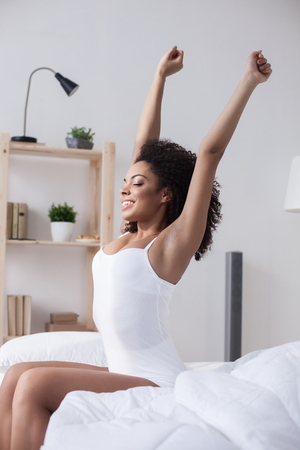 mulatto woman: Beautiful young mulatto woman is waking up with joy. She is sitting on bed and stretching her arms. The girl is smiling. Her eyes are closed with relaxation Stock Photo