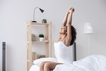 What a wonderful morning. Attractive young african woman is stretching arms after sleeping. She is sitting on bed and smiling Stock Photo - 55097074