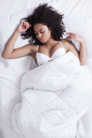 wellness sleepy: Pretty young mulatto girl is sleeping in bed. She is lying on back under the blanket