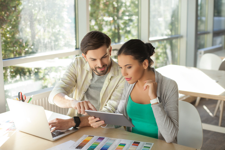 freelancers: Portrait of cheerful two freelancers creating new project. The man is pointing at the tablet and smiling. The woman is listening to him attentively