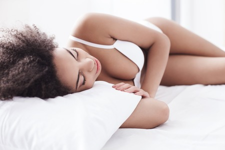 Beautiful young african woman is sleeping in bed. She is lying in white lingerie with relaxation