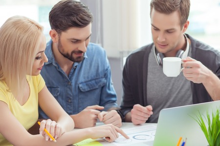 seriousness: Talented creative team is discussing their project. Woman is pointing finger at document with seriousness. Man is holding a cup and smiling