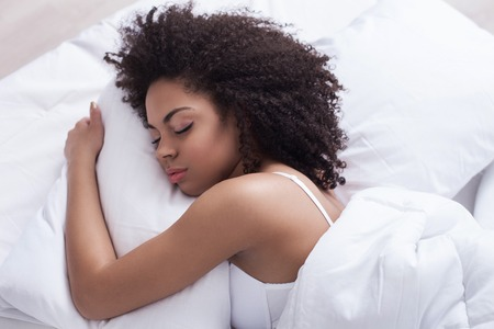 mulatto: Cute mulatto girl is sleeping in bed. She is lying and embracing the pillow with enjoyment Stock Photo