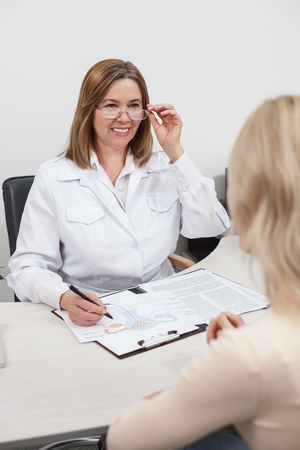 gynecologist: Experienced female gynecologist is consulting her patient. She is sitting at the desk opposite the woman. The lady is making notes and smiling