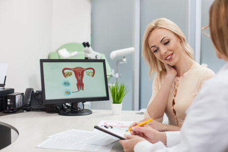 gynecologist: Professional gynecologist is consulting her patient. She is sitting at the desk and writing a prescription. The young woman is smiling