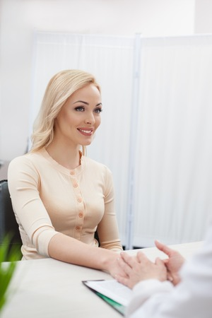 gynecologist: I rely on you. Beautiful young woman is visiting the doctor. She is holding the hand of gynecologist and looking at her with trust. The lady is smiling Stock Photo