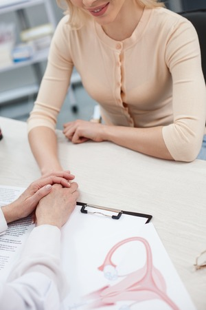 Everything will be all right. Sympathetic gynecologist is supporting her patient. She is holding female hand. The young woman is sitting and smiling Stock Photo