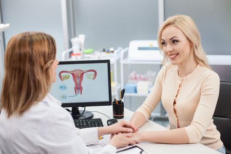 You have nothing to worry about. Cheerful female gynecologist is holding hand of young woman. The lady is looking at the doctor with trust and smiling