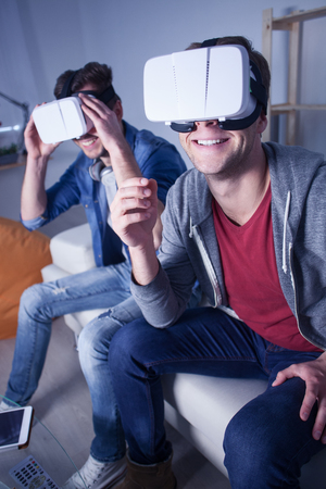 they are watching: What a cool device. Cheerful young men are watching virtual reality headset at home. They are sitting on sofa and laughing