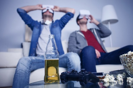 they are watching: Cheerful two friends are watching virtual reality device with joy. They are sitting on sofa and relaxing. Focus on bottle of beer, play station and popcorn on table