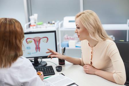 陽気な若い女性は、彼女の婦人科医にアドバイスを求めています。彼女は、机に座っては、子宮の画像をコンピューターで指を指します。女性は濃度を持つ医師を聴くこと 写真素材 - 55379296