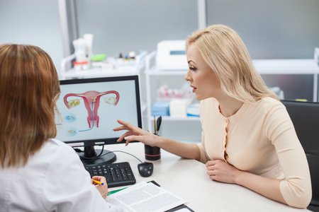 Cheerful young woman is asking advice in her gynecologist. She is sitting at the desk and pointing finger at the computer with uterus picture. Lady is listening to doctor with concentration