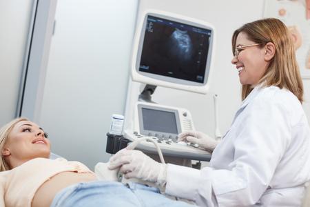 Alles is oke. Vrolijke gynaecoloog onderzoekt haar patiënt. Ze beweegt ultrasone sonde op de vrouwelijke buik en glimlachen