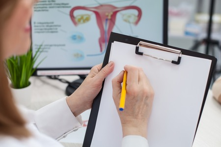 gynecologist: Close up of cheerful female gynecologist is writing a prescription. She is sitting at the desk and holding a folder of papers. The woman is smiling