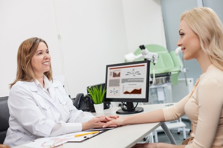 gynecologist: Professional female gynecologist is calming down her patient. She is holding her hand and smiling. The women are sitting at the desk in office Stock Photo