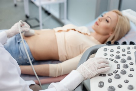 Close up of arms of gynecologist moving ultrasound transducer on female belly. The pregnant young woman is lying with joy