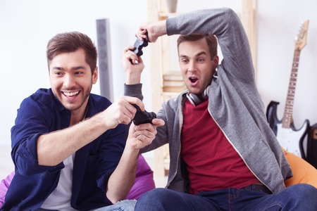 Handsome two friends are entertaining in play-station. They are looking forward with desire and smiling