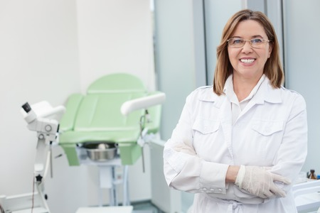 I like my work. Cheerful mature gynecologist is working in her office. She is standing and smiling. Medical chair on backgrund Stock Photo