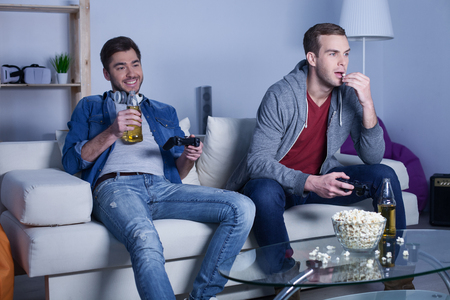 Cheerful young men are playing video games at home. They are drinking beer and eating popcorn. The man is smiling and relaxing on the couch