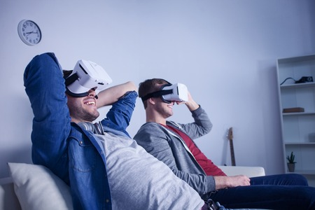 they are watching: Cute two friends are watching virtual reality device with fun. They are sitting on couch and relaxing. The men are smiling